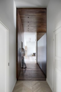 """A """"hidden"""" door to the laundry room lies along the walnut wall on one side of the hallway."""