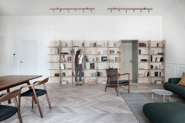 INT2 architecture used a variety of different materials to delineate spaces throughout Interior KG. The living room features a light wood herringbone parquet and several rows of shelves.