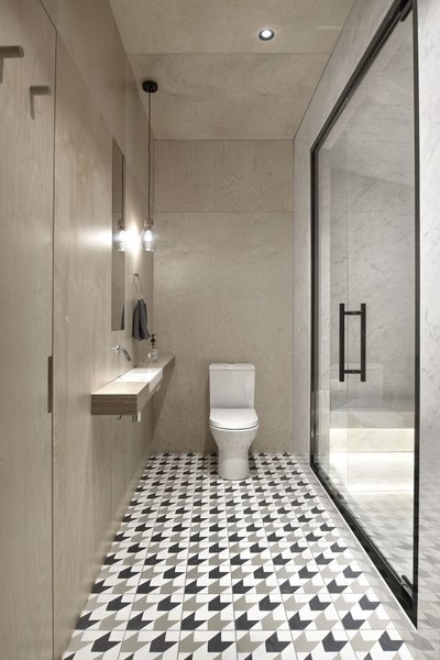 The bathrooms are visually and texturally divided into ceramic granite wet areas and painted dry areas.