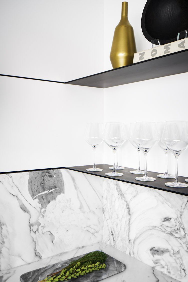 Kitchen, Marble Backsplashe, Beverage Center, Cooktops, Light Hardwood Floor, Drop In Sink, Metal Cabinet, and Marble Counter The home bar in the condo's kitchen features Carrara marble with metal shelving for a modern look.   Seaholm Custom Condo by SLIC Design