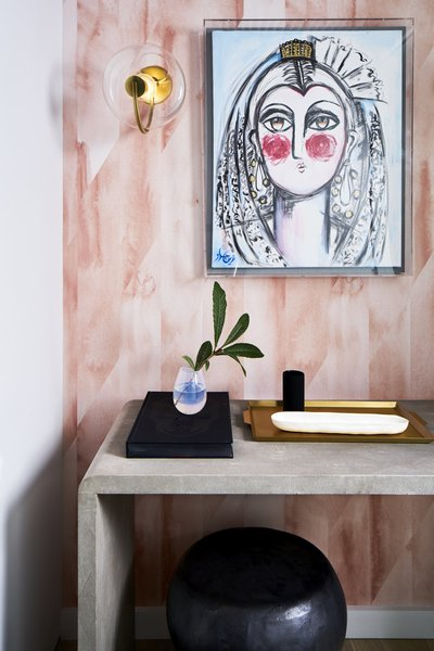 Modern entrance art and framing with a modern sconce and wallpaper.