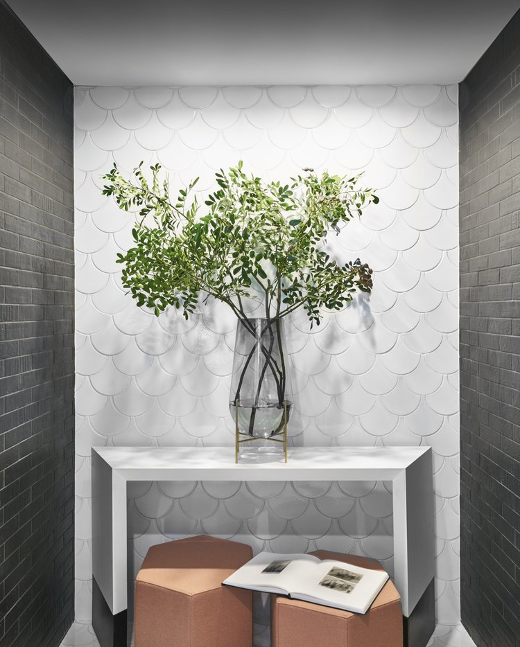 Hallway, Brick Floor, Ceramic Tile Floor, and Light Hardwood Floor Seaholm Powder Room sitting area in modern downtown Austin condo. Designed with black brick and scalloped tile walls. Featuring a vase with olive branches for an added touch.   Seaholm Custom Condo by SLIC Design