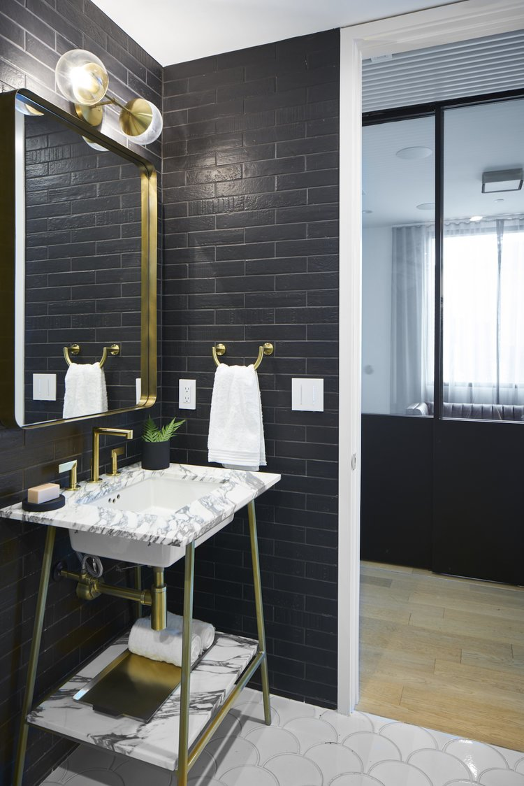 Bath Room, Drop In Sink, Ceramic Tile Floor, Stone Tile Wall, and Marble Counter Modern Seaholm Powder Room in downtown Austin condo. Featuring a Carrara marble vanity with brass hardware, black tile brick walls and scalloped floor tile.   Seaholm Custom Condo by SLIC Design