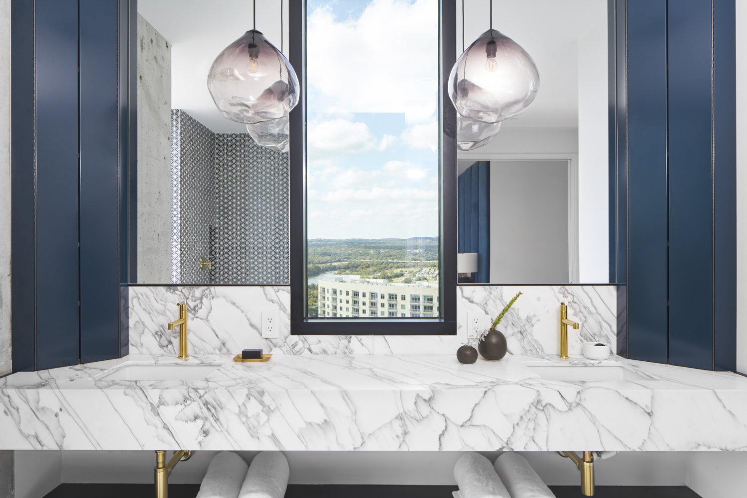 Bath Room, Marble Counter, Ceramic Tile Floor, Open Shower, Drop In Sink, and Pendant Lighting The master bathroom is designed with Carrara marble counters, blue cabinets and brass hardware sinks.   Seaholm Custom Condo by SLIC Design