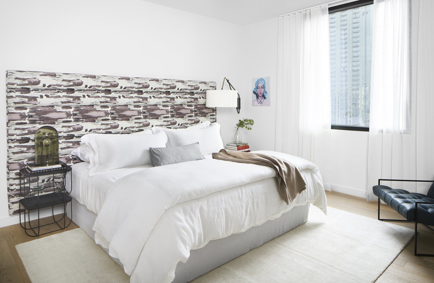 Bedroom, Rug Floor, Light Hardwood Floor, Lamps, Bed, Chair, Table Lighting, and Night Stands The guest bedroom has a wall-mounted headboard, metal night stand and white bedding with a camel throw blanket, accented with a dark teal armchair.  Seaholm Custom Condo by SLIC Design