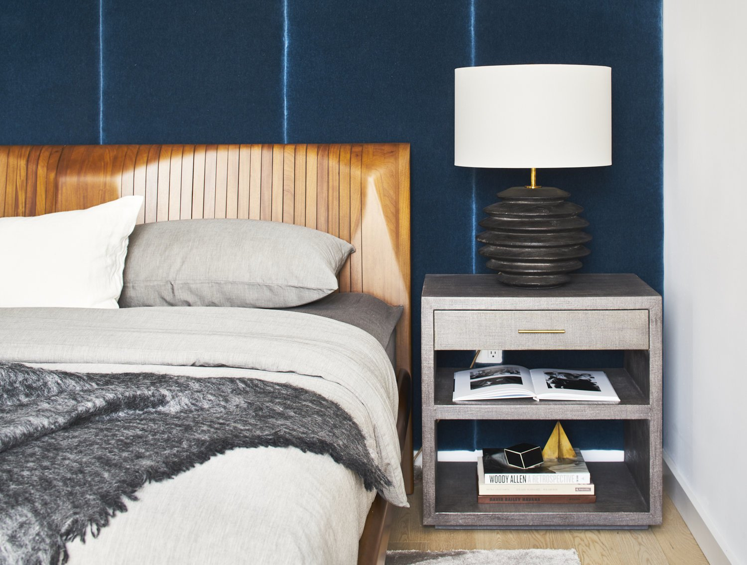 Bedroom, Night Stands, Table Lighting, Bed, Light Hardwood Floor, Shelves, and Lamps Hague Blue wall panels in master bedroom  Seaholm Custom Condo by SLIC Design