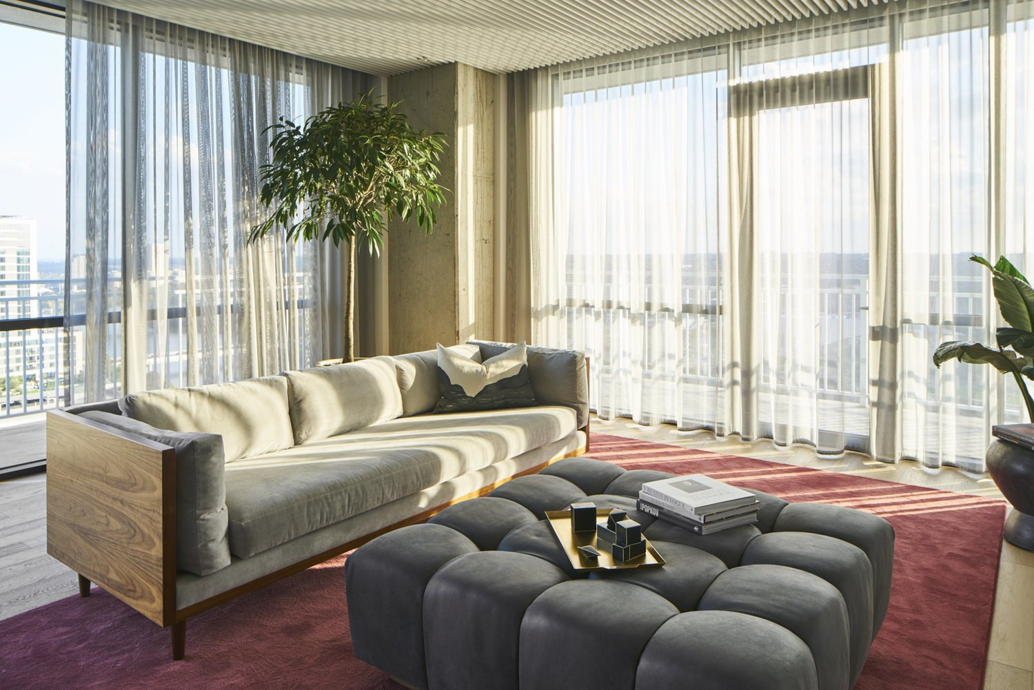 Living Room, Ottomans, Sofa, Rug Floor, Ceiling Lighting, Floor Lighting, and Light Hardwood Floor Living Room with wraparound balcony, cement walls, bubble tufted ottoman, wooden couch base, sheer curtains and red area rug.  Seaholm Custom Condo by SLIC Design