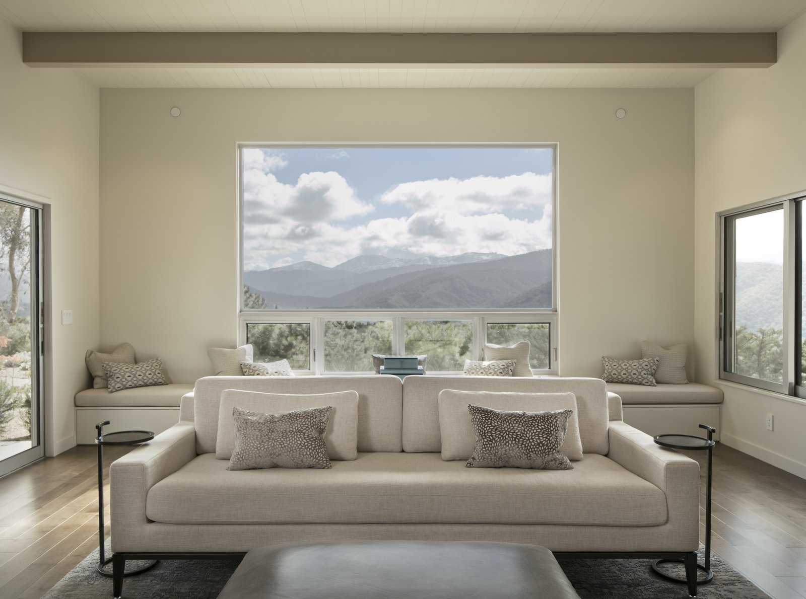 Living Room, Gas Burning Fireplace, End Tables, Ceiling Lighting, Sofa, Ottomans, and Medium Hardwood Floor Windows on three sides of the living room take advantage of mountain and valley views.   Carmel Valley Vistas