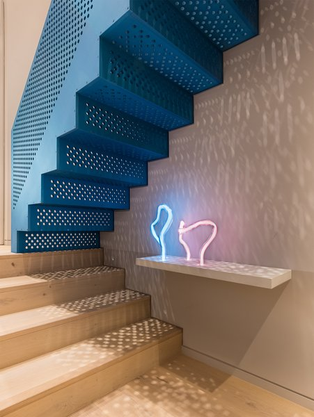Jewel in the apartment: The industrial form of the anodised aluminium staircase is precision manufactured and finished to be iridescent and soft the touch. Beneath, the ephemeral neon light contrasts with it natural flowing shape.