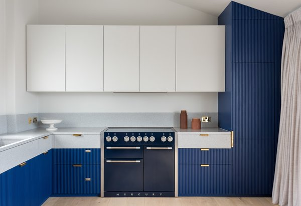 Bespoke kitchen Cabinetry: hand painted timber fluted panelling, with solid terrazzo work surface - the kitchen wraps around the room in a bold blue, anchoring it in place, yet keeping the space light