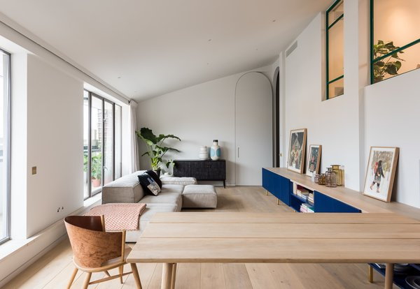 The blue cabinets of the kitchen run through into the living area with a softer natural oak top tying the room together. A modular sofa can be moved in different configurations.