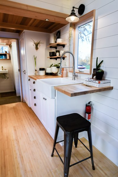 The kitchen provides a surprising amount of storage space for a tiny home. There is also a full-size sink, stove, and refrigerator.