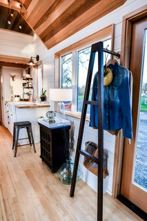 A custom coat rack at the entrance maintains the open feel.