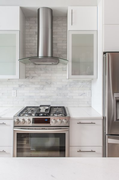 The white cabinets and traditional subway tile in marble make for a timeless combination in this kitchen in Washington, D.C.