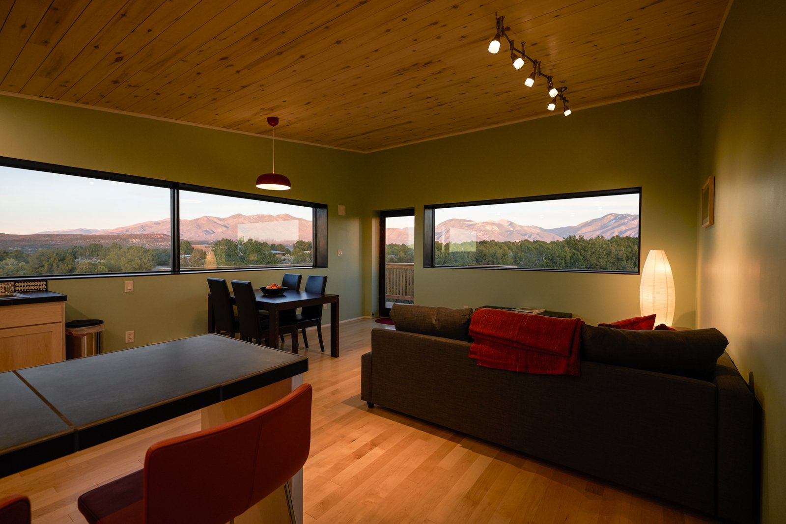 Living Room Expansive windows capturing the views of the Sange De Christo mountain Range, the Arroyo Hondo Valley and the Rio Grande.  SkyNest by Joaquin Karcher