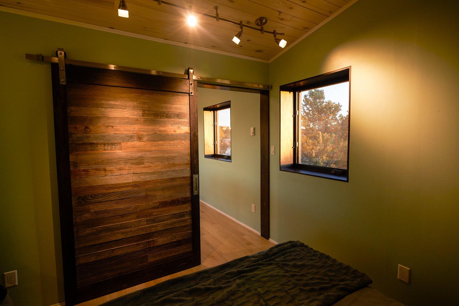 Bedroom and Light Hardwood Floor custom barn door built of reclaimed local wood  SkyNest by Joaquin Karcher
