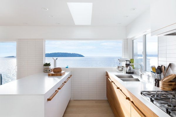 A young Vancouver family asked Falken Reynolds Interiors to convert their waterfront vacation home on British Columbia's Sunshine Coast into their primary residence. To facilitate livability for the foursome, an enlarged kitchen, complete with a large white island with wood hardware, was a major part of the renovation.