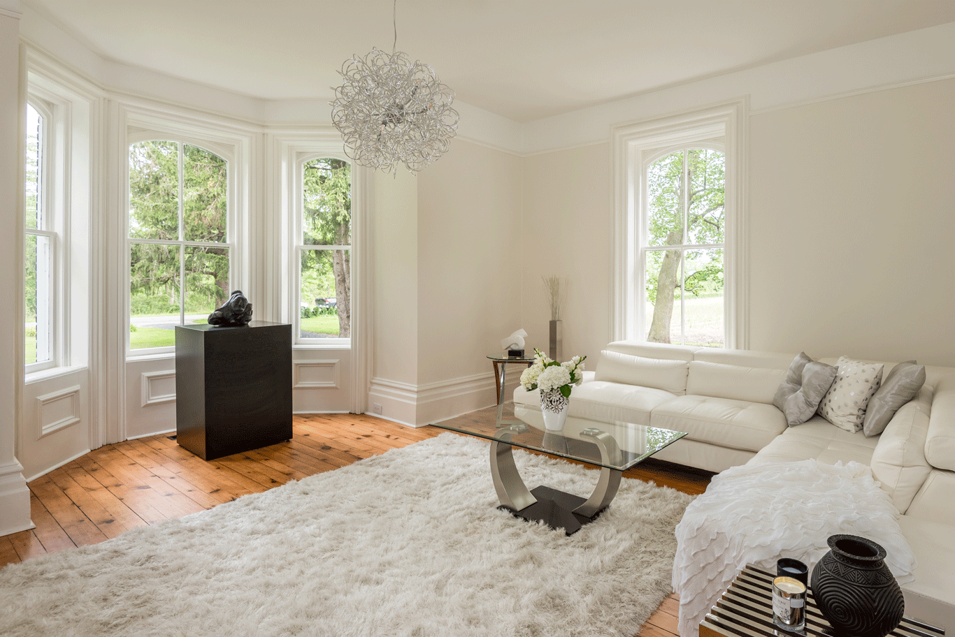 Living Room Original windows, flooring, baseboard and trim with a modern contemporary light fixture highlighting the 10ft ceilings.  The Empress by Peggy Aleksiejuk