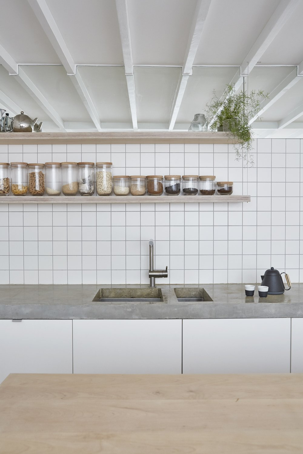 Kitchen, Wood Counter, Wood Cabinet, Drop In Sink, White Cabinet, Concrete Counter, Mirror Backsplashe, and Ceramic Tile Backsplashe Bespoke joinery, tiled finishes, concrete tops and high-level mirrors to the kitchen  Hackney Mews House by HUTCH design