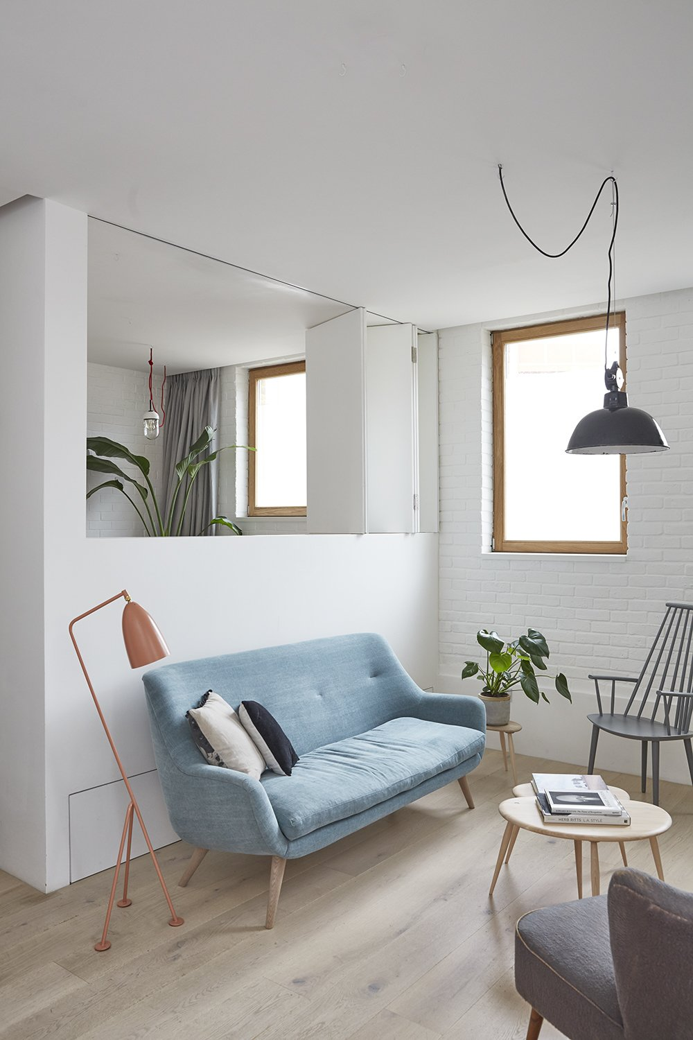 Living Room, Pendant Lighting, Sofa, Chair, Floor Lighting, Medium Hardwood Floor, and Coffee Tables The living room and home-office open up into one continuous space, or can be separated with bespoke folding doors  Hackney Mews House by HUTCH design