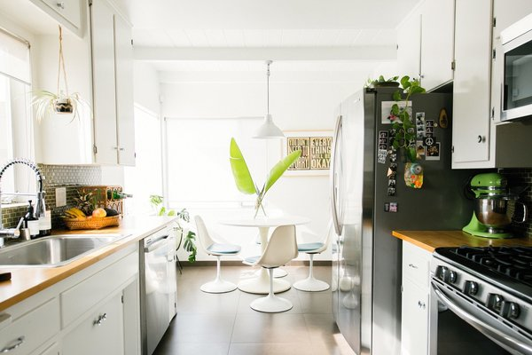 The breakfast area features vintage chairs and an Ikea table — a classic high-low mix.