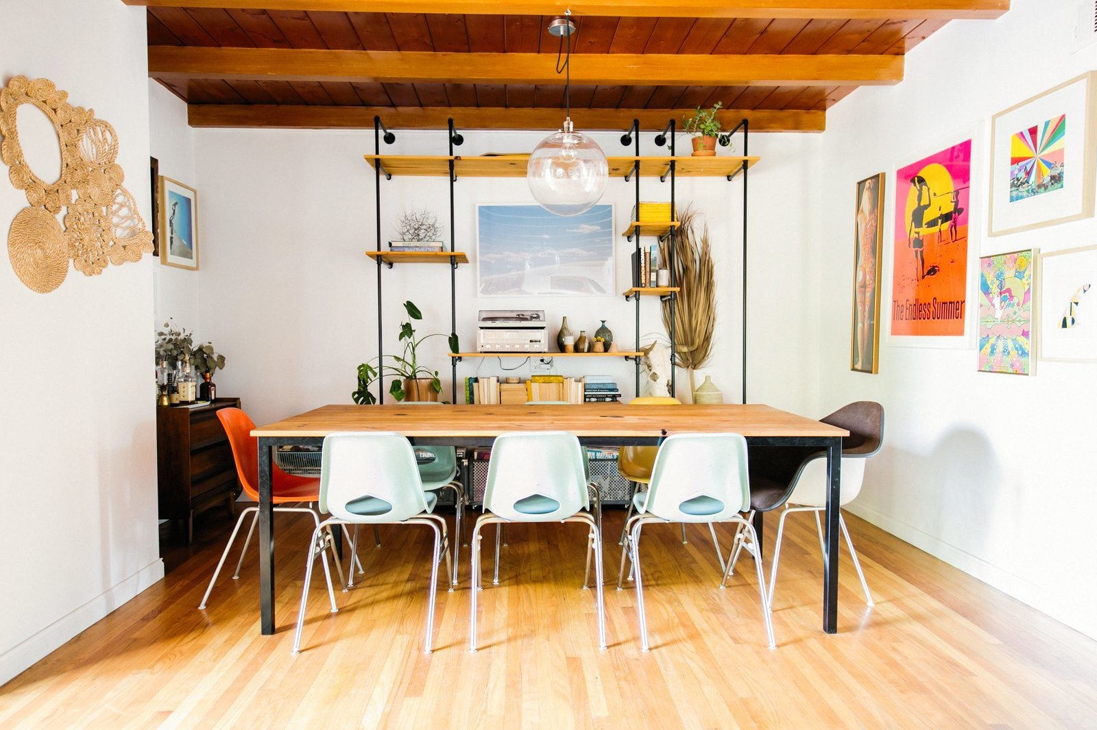 Dining Room, Medium Hardwood Floor, Pendant Lighting, Table, Shelves, and Chair Dusty also built the table and custom industrial bookshelf in the dining area.  Photo 8 of 15 in Too Cool: This Boho Surf Shack Has a Half-Pipe in the Backyard