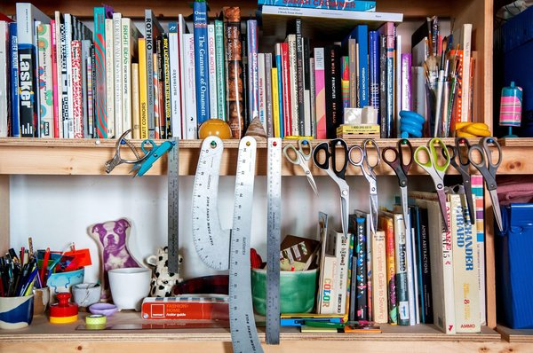 There's a sense of organization amidst the madness. A collection of scissors hang from nails hammered into a shelf packed with books seemingly arranged in no particular order — that is, until Van Dusen hardly glances when she pulls one, The Penguin Dictionary of Curious and Interesting Geometry, within seconds of referencing it.