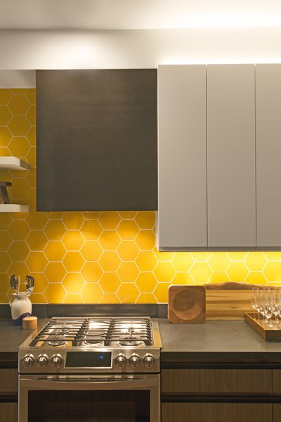 In the kitchen, the designers also considered lighting design with cabinet lighting both under and above the cabinets. The backsplash tile is by Fireclay Tile. The hood range is custom wrapped in blackened steel by Joe Chambers.