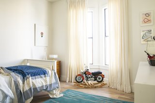 One of the boy's rooms has a simple white palette and a sea-inspired rug.