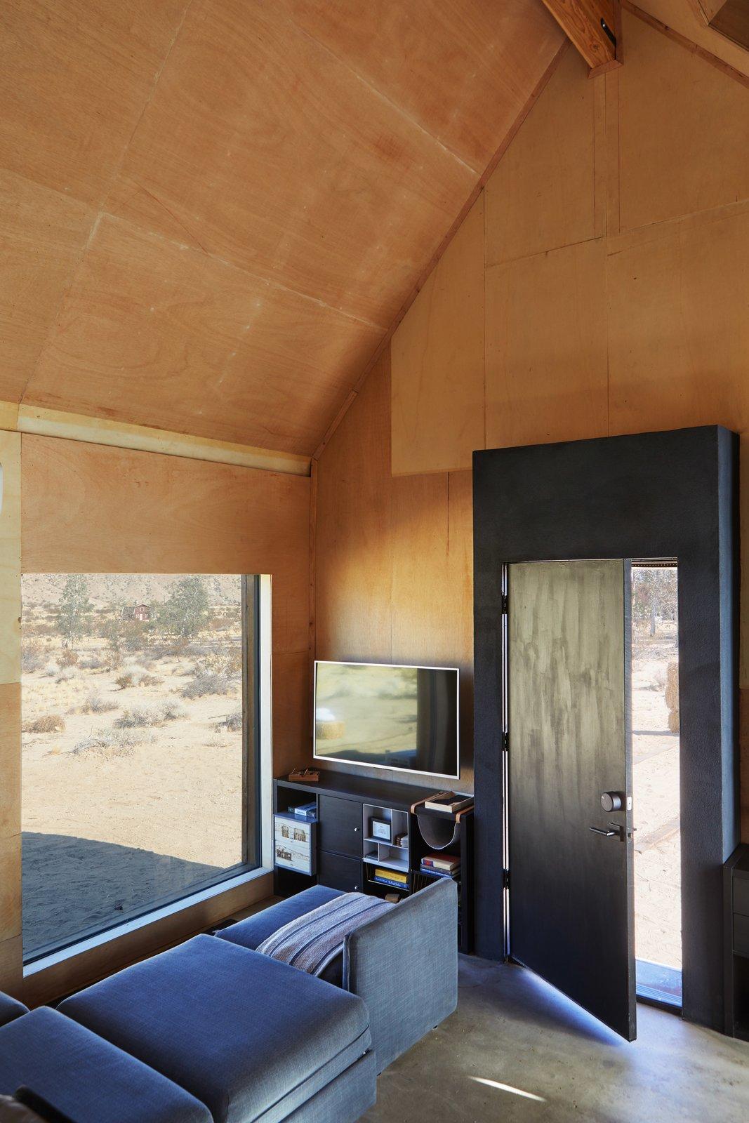 Living Room, Sofa, Wall Lighting, and Concrete Floor Living  Folly | Off Grid by malek alqadi