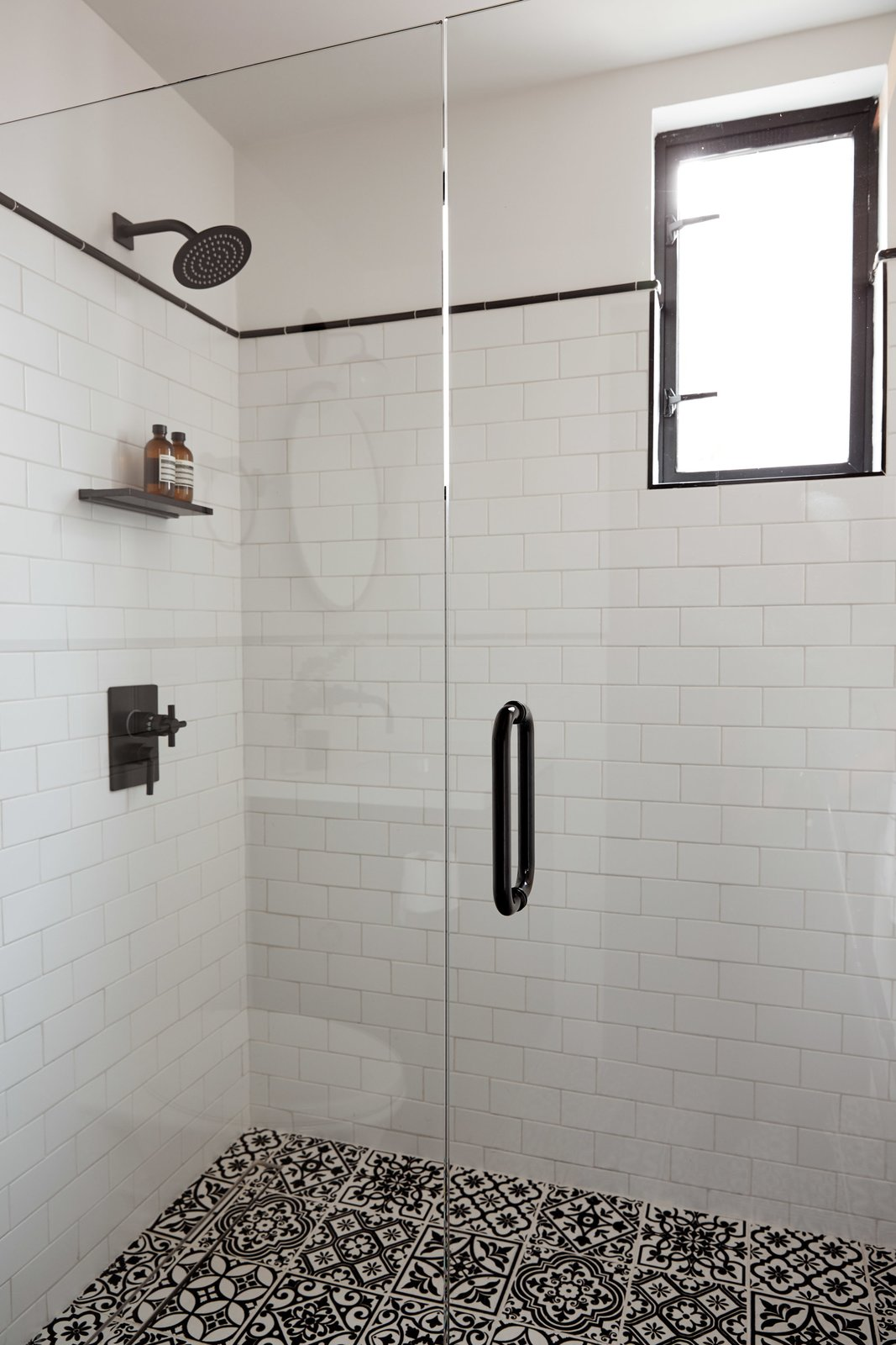 Bath, One Piece, Wall, Undermount, Enclosed, Ceramic Tile, Tile, and Porcelain Tile The walls use white subway tiles with black accent trim molding, and the floor features decorative artisan glazed tiles with raised surface patterns.  Best Bath Enclosed Wall Tile Undermount Photos from Normal Heights Residence