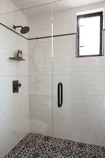 The walls use white subway tiles with black accent trim molding, and the floor features decorative artisan glazed tiles with raised surface patterns.