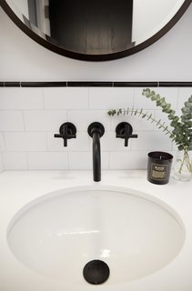 Black powder-coated faucets contrast the white sink and tiles.