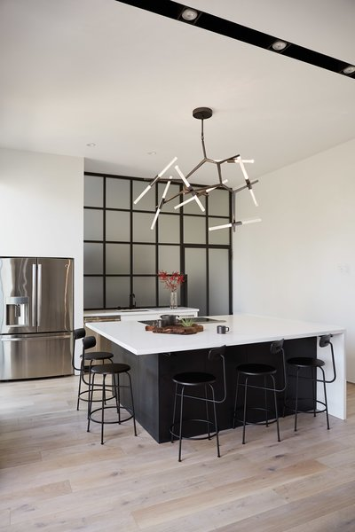 The minimal and functional kitchen features a built-in island that seats 5-6, but more often it serves as a prep-working surface for catered parties.