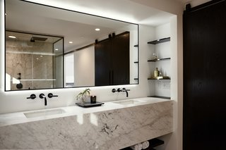 The master bathroom features a marble vanity with a mitered edge, with open shelves on the sides. To emphasize a minimalistic look, the custom steel-framed mirror is backlit with LED lights. A bi-parting sliding door made of black stained wood separates the toilet room and laundry room.