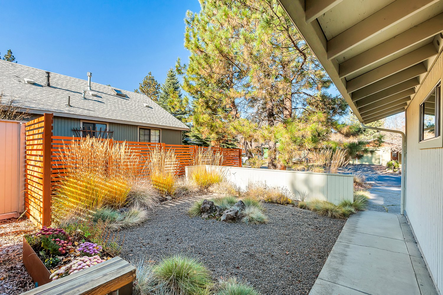 Outdoor, Stone Patio, Porch, Deck, Front Yard, Hardscapes, Boulders, Wood Fences, Wall, and Horizontal Fences, Wall Low-maintenance landscaping with native plants.  The Mod Ranch