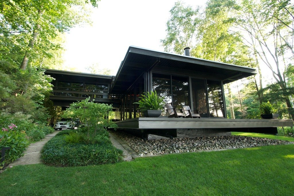 Exterior, Metal, Mid-Century, Metal, House, and Flat Lake/Front view showing living room windows surround.  Best Exterior Metal Mid-Century Flat Photos from The T-House
