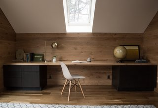 This contemplative home office design and layout by Morgan Studio Architecture & Interiors incorporates modern home office ideas featuring a classic Eames chair, warm wood paneling, and brass details. The ample skylight makes for a natural task light.