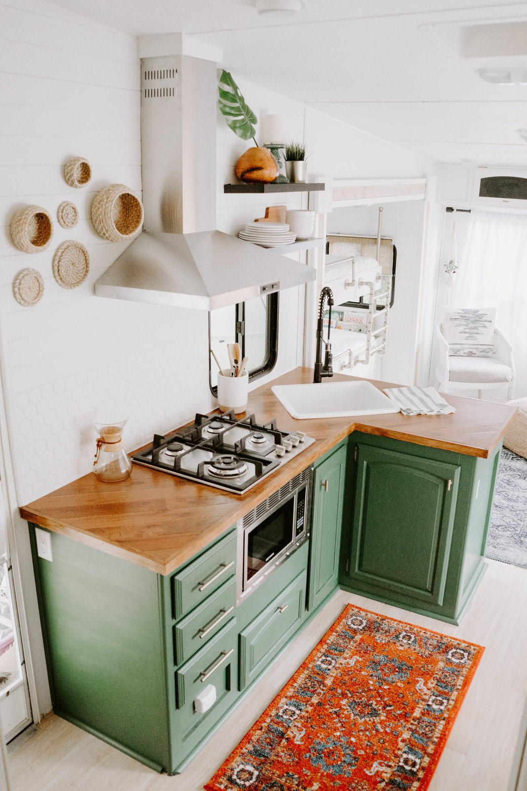 "Kitchen, Light Hardwood, Range Hood, Microwave, Cooktops, Ceramic Tile, Drop In, Colorful, Wood, Ceiling, and Rug ""Nobody thought it could be done,"" states Lauren. ""I painted the design plans and posted them on our social media. I'm positive people thought we were foolish wanting to make this old RV look like a tiny home, but voila—isn't she a beauty?""    Best Kitchen Microwave Drop In Range Hood Colorful Photos from The Cougar"