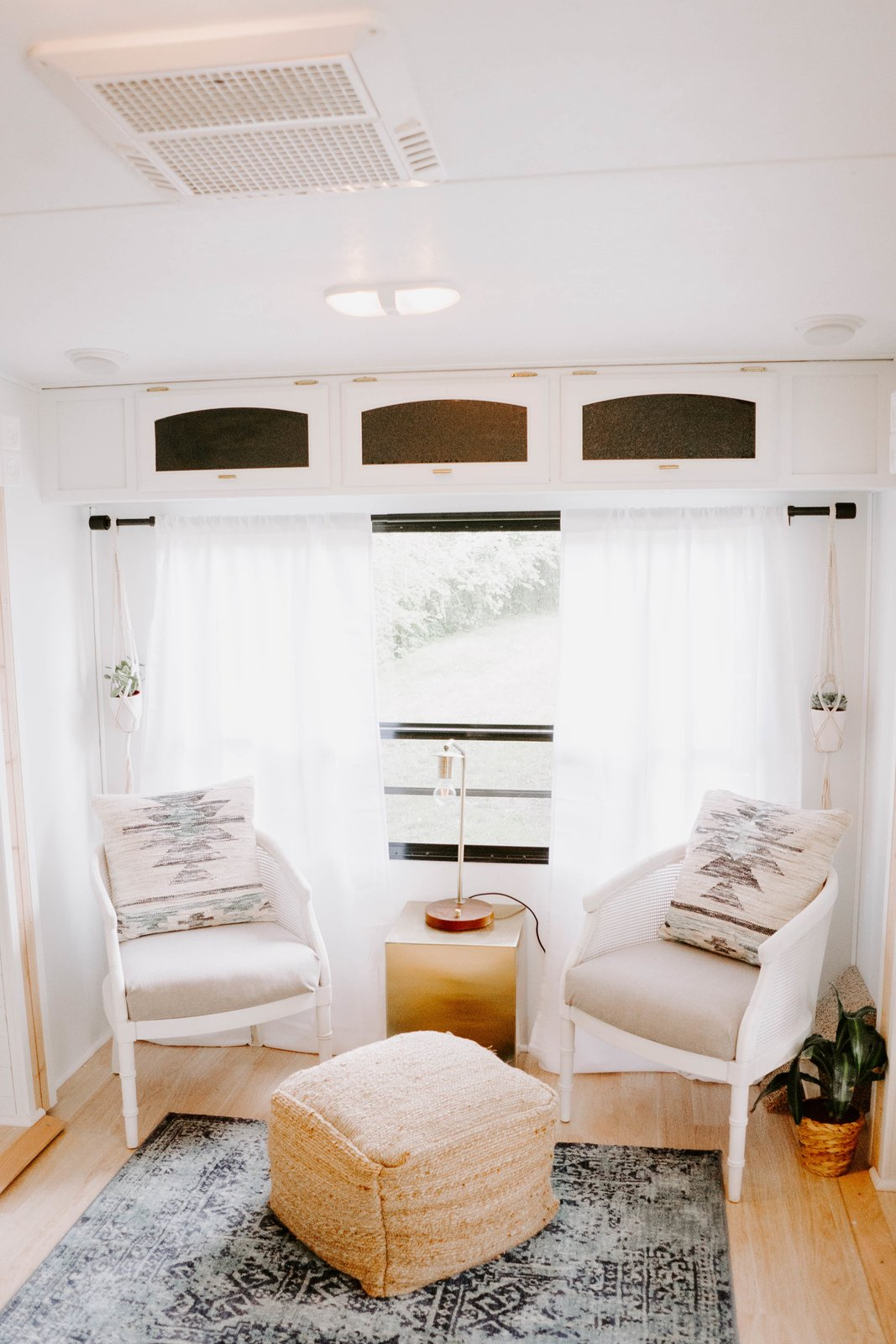 Living Room, Chair, Table Lighting, Light Hardwood Floor, Ottomans, Ceiling Lighting, Lamps, Rug Floor, and End Tables This area now makes a beautiful spot to curl up and read a book.    Photo 6 of 14 in Embark on Your Next Road Trip in This Renovated Camper For $35K from The Cougar