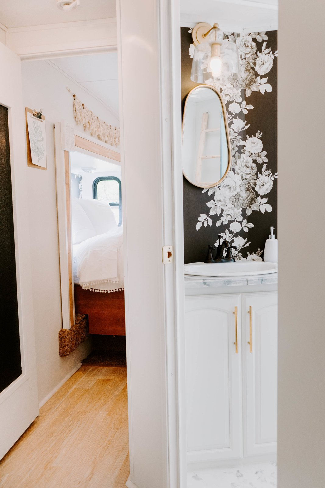 """Bath Room, Wall Lighting, Marble Counter, Drop In Sink, and Porcelain Tile Floor """"The bathroom may have been my favorite transformation,"""" explains Lauren. """"I spotted some beautiful inspiration from Studio McGee and I was hooked on the floral wallpaper idea.""""    Photo 10 of 14 in Embark on Your Next Road Trip in This Renovated Camper For $35K from The Cougar"""