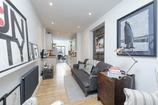 The oak flooring and inset, exposed brick wall add warmth and character to the living space.