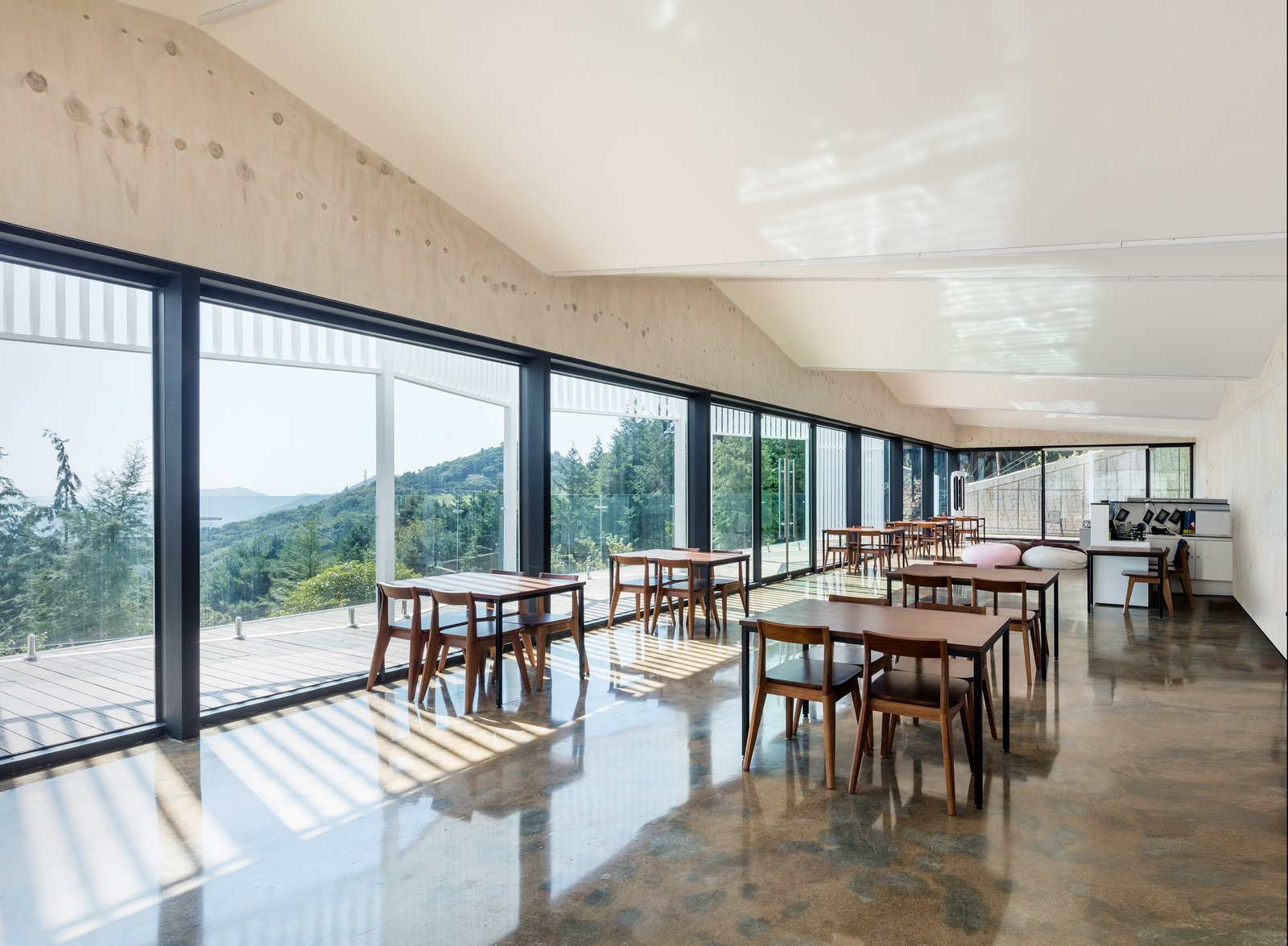 Dining Room, Table, Travertine Floor, and Chair The glazed walls make the dramatic natural scenery the centerpiece of the room.  Photo 7 of 7 in Colorful Glamping Pods Dot a Forest in South Korea