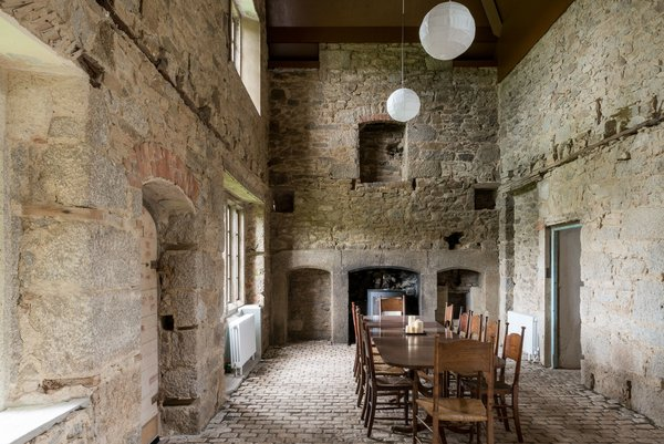 The most dramatic room in the main house is the dining room, which features a soaring, pitched ceiling and exposed stone walls.