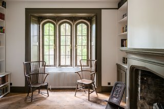The wooden Windsor chairs placed by the recessed shuttered windows in the study create a cozy reading corner.