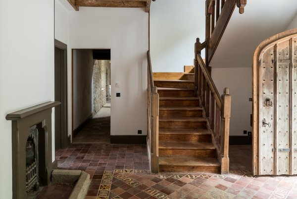 The oak staircase, arched studded front door, and decorative floor tiles in the hallway have a wonderful handcrafted look.