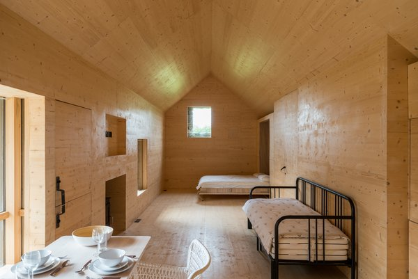 The interior of this studio building is clad in birch plywood, giving it the appearance of an Nordic wilderness cabin.