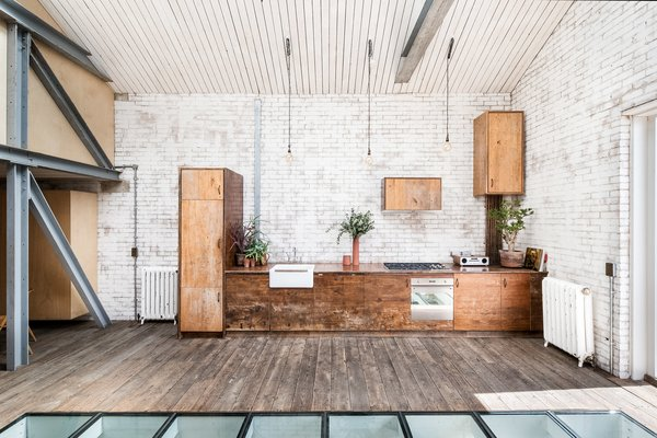 The kitchen area is full of charm, starting with the original painted brick wall and continuing with cabinets made from reclaimed Iroko wood. The uneven application of paint mimics the aged wood.