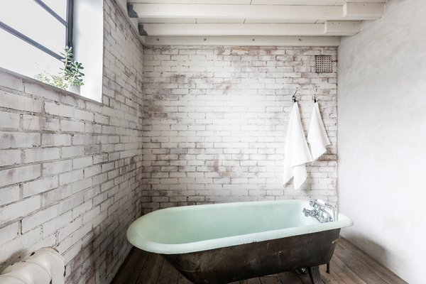 Housed underneath the mezzanine level, the bathroom features whitewashed walls and an elegant, freestanding bath.