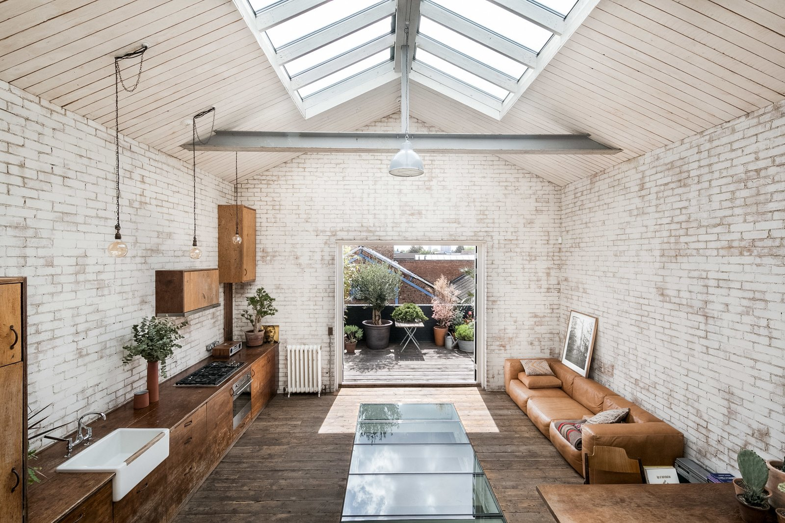 Living Room, Pendant Lighting, Dark Hardwood Floor, Coffee Tables, and Sofa The mezzanine bedroom has elevated views across the living space, the decked terrace, and the city skyline beyond.  Photo 2 of 11 in Snap Up This Converted  Warehouse in London For $2.1M